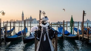 A woman dressed in Carnival costume poses in front of gondolas in Saint Mark's Square in Venice