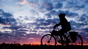 A woman is silhouetted against the sunrise coloured sky as she rides her bicycle near Hannover in Germany (Pic: EPA)