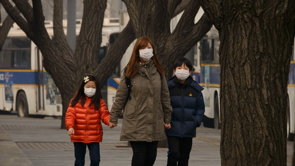 A mother and her two children wear face masks as they walk during heavily polluted weather in Seoul in South Korea
