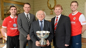 President Michael D Higgins holds the President's Cup, with Gavin Peers, Ian Baraclough, Liam Buckley and Greg Bolger