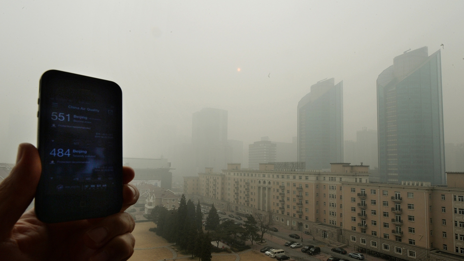 A phone shows the US embassy pollution index reading of 551, which is extremely hazardous, and the Chinese government reading of 484, as heavy air pollution continues to shroud Beijing