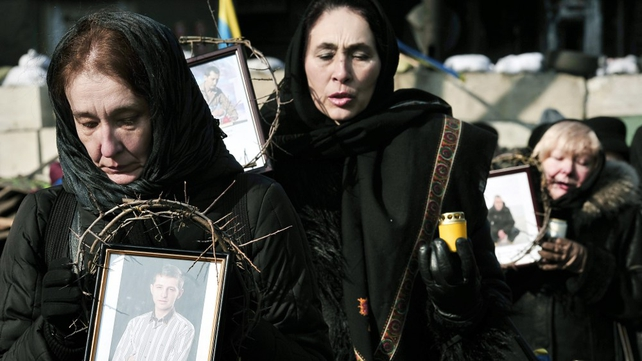 Women hold pictures of victims of last week's violence while walking in procession in central Kiev