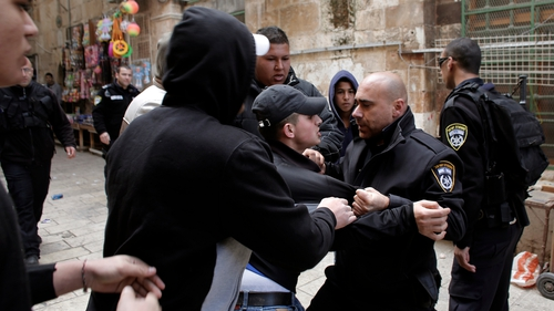 Palestinian men scuffle with Israeli police at an alleyway leading to the al-Aqsa Mosque compound
