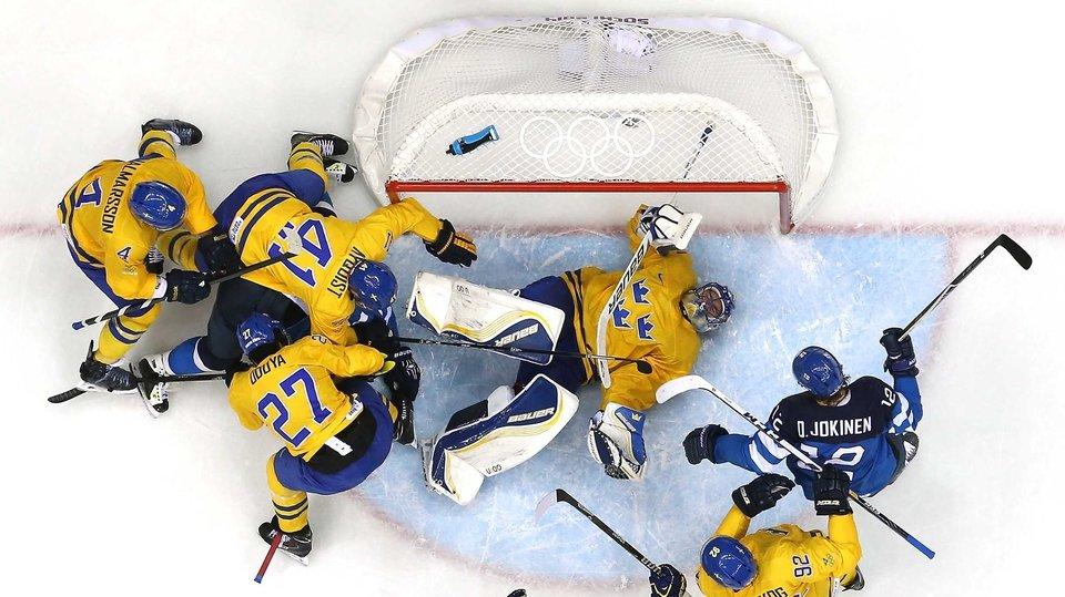 Olli Jokinen of Finland looks on as Henrik Lundqvist of Sweden lies in the crease during the Men's Ice Hockey semi-final
