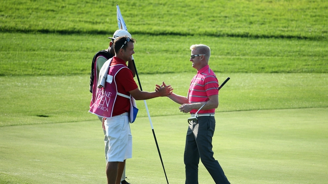 Simon Dyson shakes hands with his caddie on the 18th green