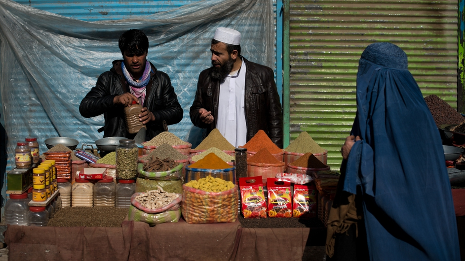 An Afghan street vendor sells spices to a customer as a pedestrian walks by in Kabul