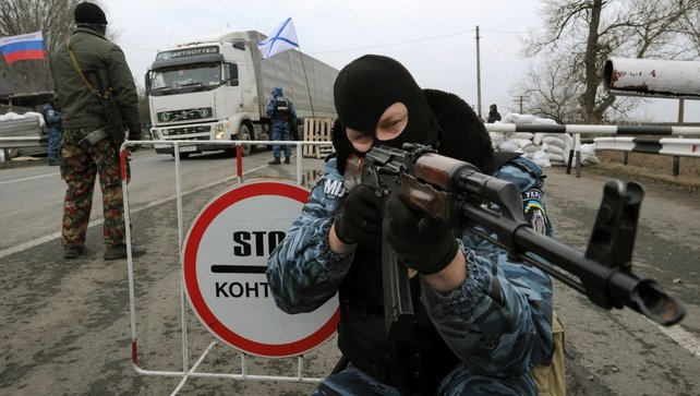Armed masked man aims his Klashnikov rifle at a checkpoint under a Russian national (L) and Russian naval (R) flags