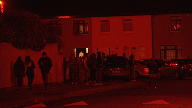 People gathered outside his brother's home where he was shot before 6pm this evening