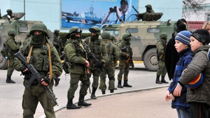 Young boys look on as unidentified armed individuals block the center of Balaklava, near Sevastopol