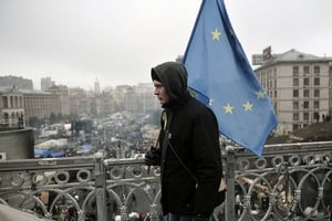 A man walks with an EU flag at the bridge overlooking the Independence square in central Kiev