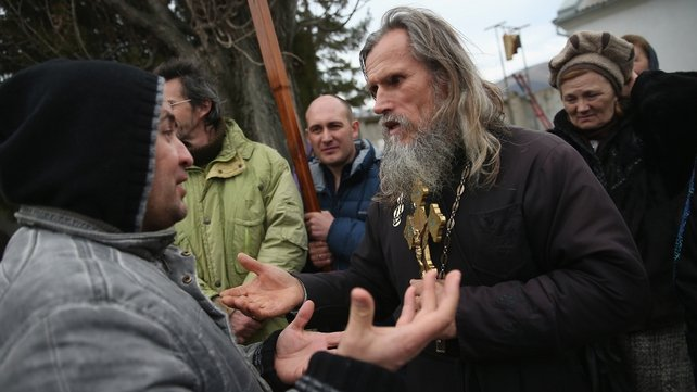A pro-Russian man (L) argues with an Orthodox priest outside a Ukrainian military base