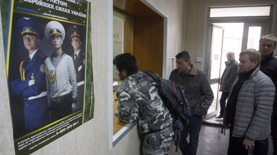 Men queue at the reception of a military enlistment office in Kiev, after all military reservists were called up