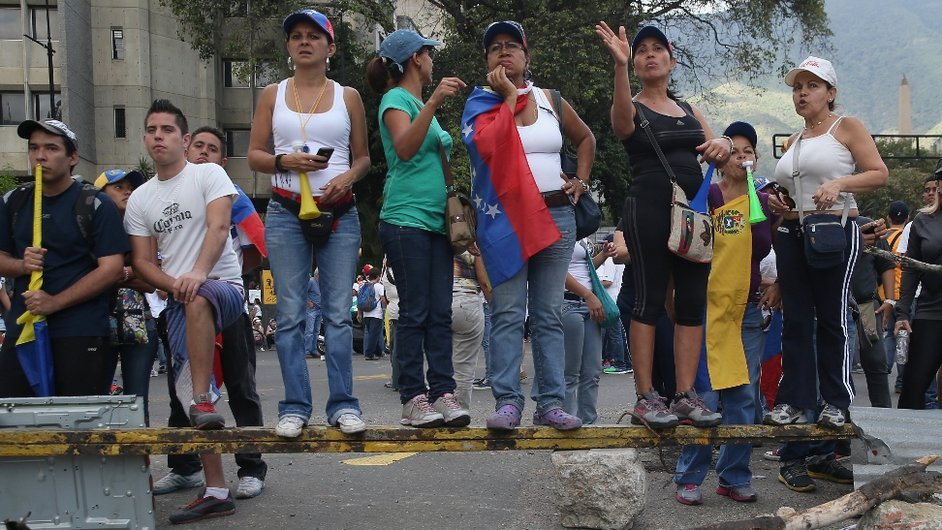 Protesters stand on top of a barricade during an anti-government demonstration in Caracas, Venezuela