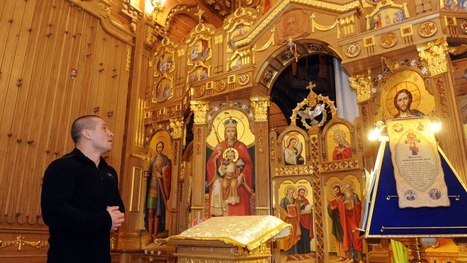 A man looks at icons in a chapel of the main house