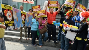 Filipino activists dressed as clowns and holding water pistols spray a map illustrating China's claim to the South China Sea during a protest in front of the Chinese consular office in the financial district of Manila