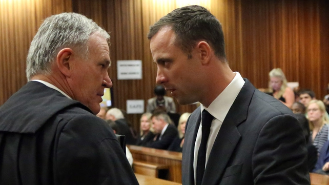 Mr Pistorius speaks to the leader of his defence team, lawyer Barry Roux, while standing in the dock
