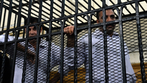 Two policemen Mahmoud Salah (L) and Awad Ismael (R) stand inside a court cage during their trial