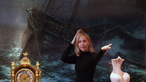 A Christie's employee stands in front of a piece by Jonathan Wateridge entitled Shipwreck at Christie's auction house in London