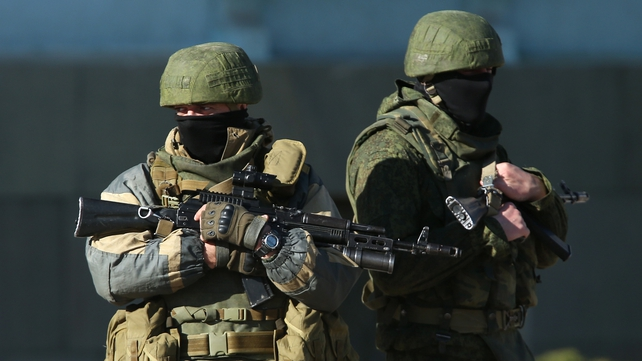 Heavily-armed troops stand guard outside a local government building in Simferopol