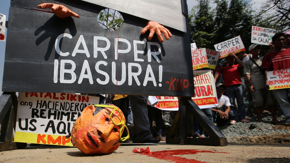 Filipino farmers decapitate an effigy of President Benigno Aquino III during a protest calling for reforms in Manila (Pic: EPA)