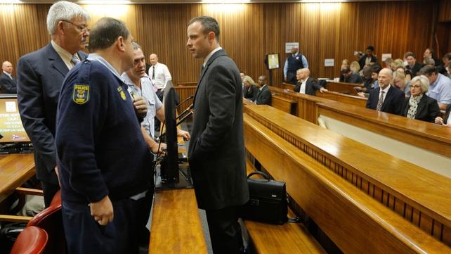 Mr Pistorius speaks to his defence team