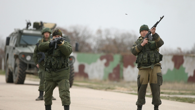 Troops under Russian command fire weapons into the air and scream orders to turn back at an approaching group of over 100 hundred unarmed Ukrainian troops at the Belbek air base