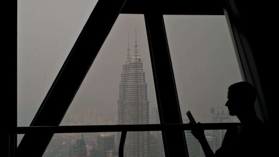 Malaysia's landmark Petronas Twin Towers are seen covered in haze as a tourist sits on the KL Tower observation deck in Kuala Lumpur