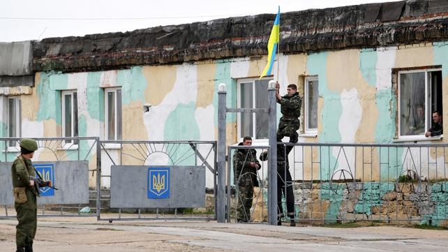 Ukrainian troops unfurl a Ukrainian flag near the entrance of the Ukrainian military air base outside Sevastopol
