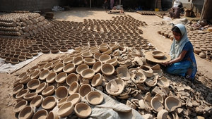 Sana, a grand-daughter of Pakistani artisan Mariam Bibi, prepares pots for drying at their small workplace in Karachi