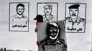 A Yemeni graffiti artist holding a stencil passes portraits of the victims of an al-Qaeda attack on Yemen's Defence Ministry's complex on a wall during an anti-terrorism campaign in Sana'a (Pic: EPA)