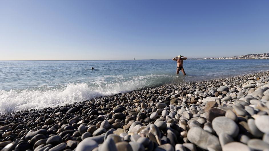 People enjoy warm temperatures on the beach in the French Riviera city of Nice