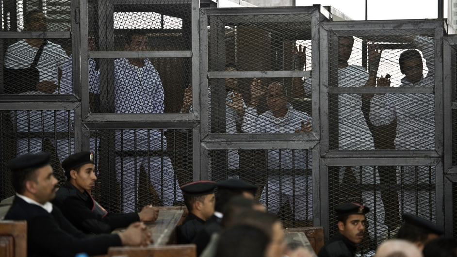 Australian journalist Peter Greste (C) of Al-Jazeera and his colleagues stand inside a cage during their trial in Cairo for allegedly supporting the Muslim Brotherhood