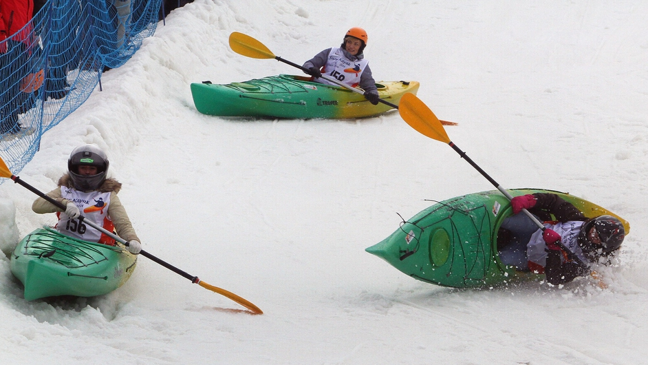Participants in a snow kayak race compete at the alpine skiing track in Druskininkai in Lithuania