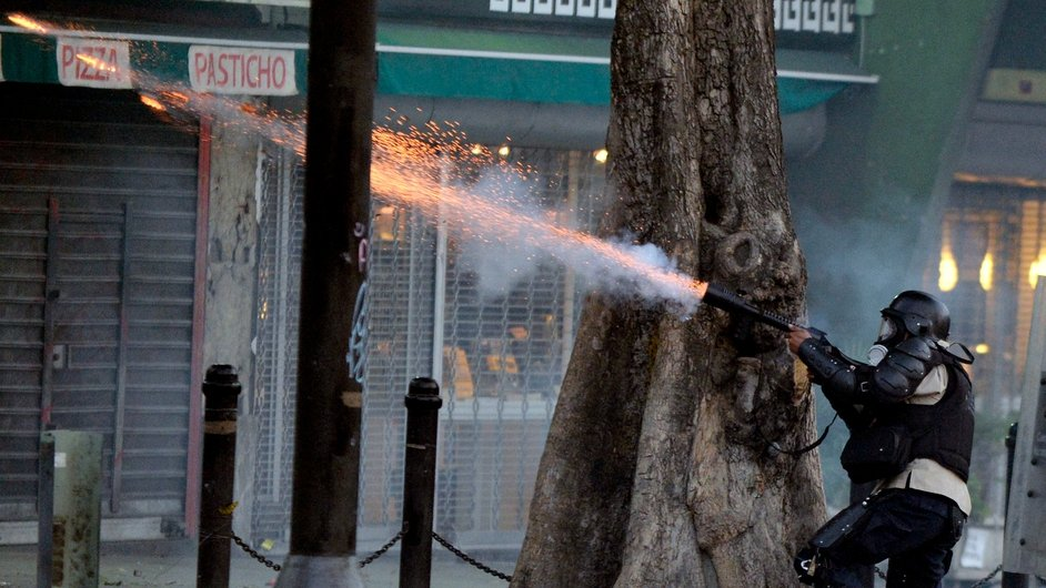 A policeman shoots tear gas at opposition activists during a protest against the government of Venezuelan President Nicolas Maduro in Caracas