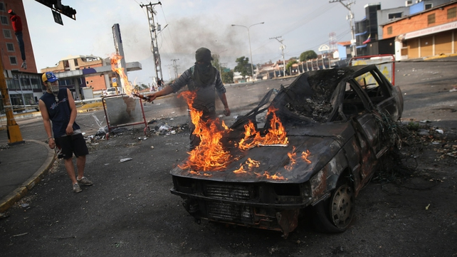 A protester throws gasoline on a burned out car during an anti-govenment protest in San Cristobal