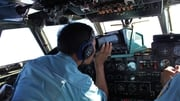 Military personnel scan the sea aboard a Vietnamese Air Force aircraft in the search for flight MH370