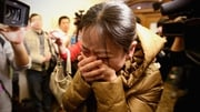 A relative of a passenger onboard Malaysia Airlines flight MH370 cries at a local hotel where families are gathered