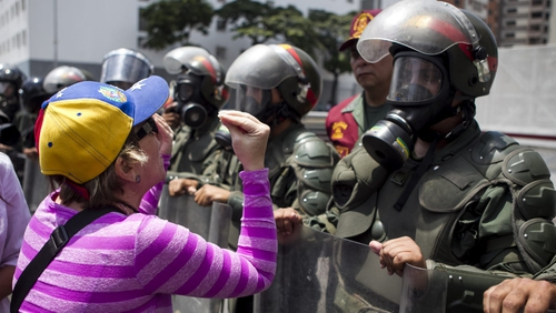 A woman protests in front of members of the Bolivarian National Guard during a demonstration in Caracas (Pic: EPA)