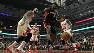 Carlos Boozer (l) and Jimmy Butler of the Chicago Bulls watch as LeBron James of the Miami Heat looses the ball out of bounds