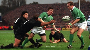 Two men tackle O'Driscoll but, typically, he still gets his pass off against New Zealand in 2001