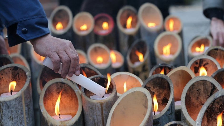 A man lights a bamboo a candle to commemorate victims in front of Kobe's light of hope memorial