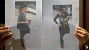 A Malaysian police official displays photographs of the two men who boarded flight MH370 using stolen European passports