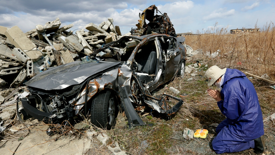 Koichi Yamada offers a prayer for his friend Kenichi Sato, who was killed by the tsunami, at his friend's destroyed car in the tsunami-devastated Ukedo area in Namie, Fukushima Prefecture (Pic: EPA)
