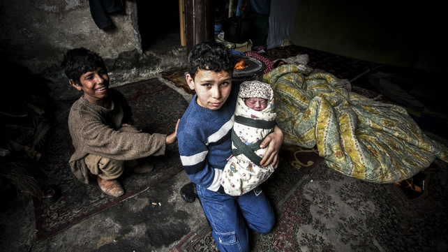 A Syrian refugee boy poses with his newborn brother as their mother lies near them in a house in the Basaksehir district of Istanbul