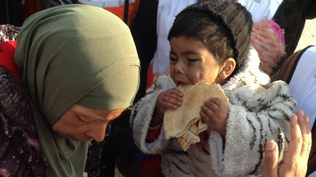 A child eats bread before being evacuated from the besieged Yarmuk Palestinian refugee camp, south of the Syrian capital, Damascus