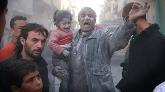 A man holds a crying girl as he gestures following an air strike by government forces on the Sahour neighbourhood of Aleppo