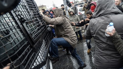 Turkish protesters attack a riot police vehicle during clashes outside the Okmeydani Hospital
