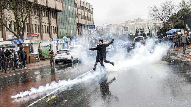 A demonstrator kicks a tear gas canister after the police fired them at a crowd outside the Istanbul hospital