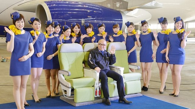 Skymark president Shinichi Nishikubo poses with cabin crew