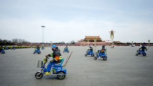 A group of cleaners clean the ground as they ride tricycles after the closing session of the Chinese People's Political Consultative Conference (CPPCC), in Tiananmen Square in Beijing